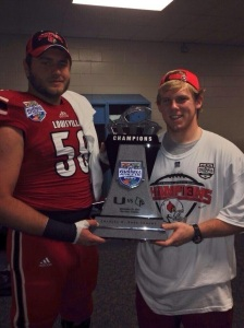 Luke Brohm and Andrew Polston with the 2014 Russell Athletic Bowl Trophy | Photo from Twitter.com